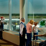 Photo of people looking at airplanes through the window of the public observation deck in the terminal building thumbnail