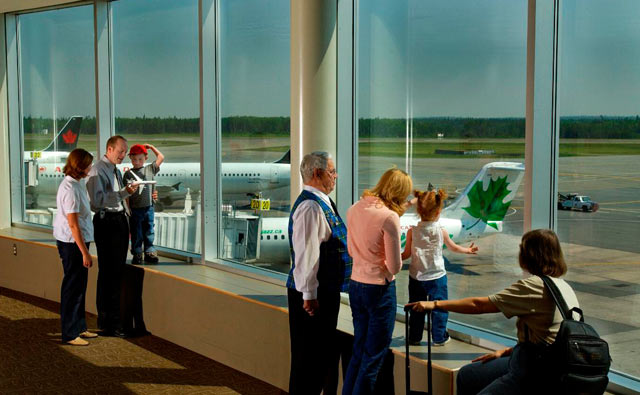 Photo of people looking at airplanes through the window of the public observation deck in the terminal building