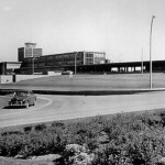 1960's photo of a car leaving the airport with the termina building in the background thumbnail